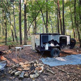 Teardrop camper and the nature background: woods and a campfire spot | Boreas Campers Homepage
